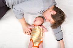 有新出生的小女儿的,家庭画象愉快的骄傲的年轻父亲一起 免版税库存照片