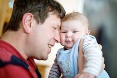 有新出生的小女儿的,家庭画象愉快的骄傲的年轻父亲一起 库存照片