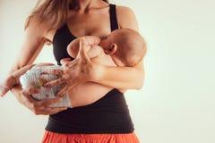 有新出生的小婴儿的愉快的母亲在站立和breasfeeding lacting的哺乳期健康和关心接合时间的手上 图库摄影