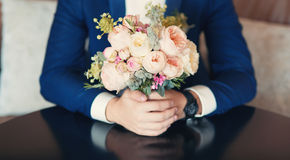 有新娘婚礼牡丹花束的一个新郎在他的手上 免版税库存图片