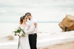 有新娘的年轻夫妇新郎一个沙滩的 免版税库存照片