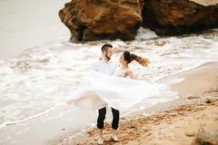 有新娘的年轻夫妇新郎一个沙滩的 免版税库存图片