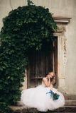 有新娘花束的美丽的年轻白肤金发的新娘坐台阶在华美的植物下 库存图片
