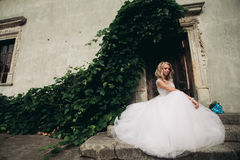 有新娘花束的美丽的年轻白肤金发的新娘坐台阶在华美的植物下 免版税库存照片