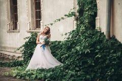 有新娘花束的美丽的年轻白肤金发的新娘坐台阶在华美的植物下 图库摄影