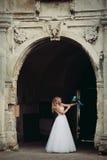 有新娘花束的美丽的年轻白肤金发的新娘坐台阶在华美的植物下 免版税库存图片