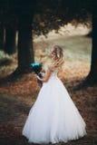 有新娘花束的美丽的年轻白肤金发的新娘坐台阶在华美的植物下 免版税图库摄影