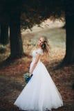 有新娘花束的美丽的年轻白肤金发的新娘坐台阶在华美的植物下 库存照片