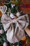 有新年手工制造麻袋布弓的手 库存照片