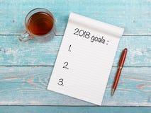 有新年目标的笔记本在2018年与一个杯子thee和在一张蓝色木桌上的一支笔 免版税库存图片