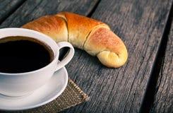 有新月形面包早餐的咖啡杯 库存图片
