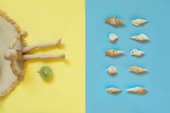 有新柠檬酸饮料的木玩偶在黄色当沙子海滩和蓝色作为水 概念棕褐色和海滩 紫外防护 夏天 梦想 免版税库存图片