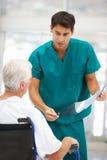 有新男性医生的高级患者 库存照片