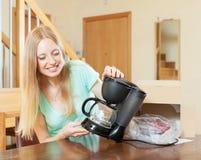 有新的咖啡机器的少妇在家庭内部 库存照片