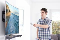 有新的弯曲的屏幕电视的年轻人在家 库存照片