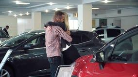 有新的汽车的人惊奇的妇女在展示屋子里 免版税库存图片