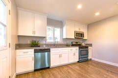 有新的装置和木地板的式样厨房 免版税库存照片