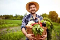 有新近地被采摘的菜的农夫在篮子 免版税库存照片