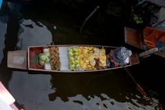 有新鲜农产品的销售人在一条小船在Thailand's浮动市场上 免版税库存图片