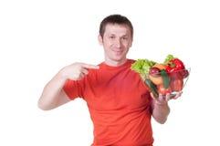 有新鲜的健康菜板材的年轻人  库存图片
