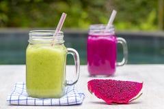 有新鲜的圆滑的人的两个玻璃杯子从龙结果实,香蕉、芒果、鲕梨、硬花甘蓝和蜂蜜 海岛巴厘岛, Ubud,印度尼西亚 库存图片
