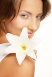 有新鲜的干净的皮肤和白花的少妇 免版税图库摄影