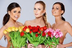 有新鲜的春天郁金香的三名美丽的妇女 库存照片