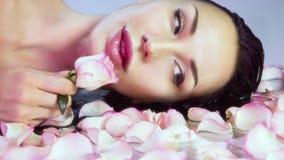 有新鲜的玫瑰花瓣和桃红色玫瑰花蕾的妇女 自然罗斯wate 免版税库存照片