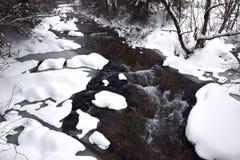 有新鲜的雪的小结冰的河在岩石 图库摄影