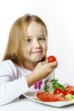 有新鲜蔬菜板材的逗人喜爱的小女孩  免版税库存照片