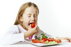 有新鲜蔬菜板材的逗人喜爱的小女孩  免版税库存图片