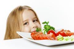 有新鲜蔬菜板材的逗人喜爱的小女孩  库存照片