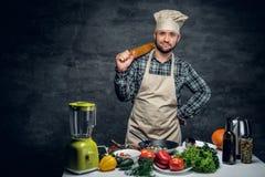 有新鲜蔬菜的一个厨师人在桌上 免版税库存照片