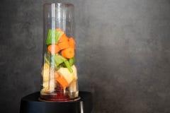 有新鲜蔬菜的搅拌器 切的芹菜、苹果和红萝卜在一个搅拌器杯子圆滑的人的 r r 免版税库存图片