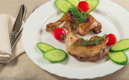 有新鲜蔬菜的烤鸡腿 在餐巾的刀子 库存图片