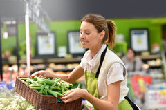 有新鲜蔬菜篮子的超级市场雇员  免版税图库摄影