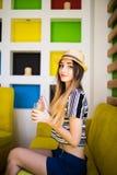 有新鲜水果汁杯子佩带的帽子的俏丽的妇女在咖啡馆 库存照片