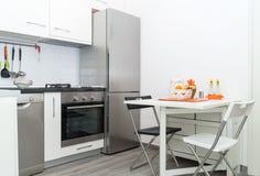 有新鲜水果篮子的厨房在与两把椅子的白色表上 库存图片