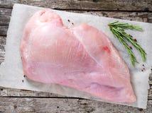 有新鲜rosmary的未加工的整个大乳房火鸡内圆角在老土气灰色木背景 顶视图 免版税图库摄影