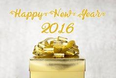 有新年快乐2016词的金黄当前箱子在bokeh光 免版税库存照片