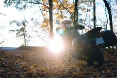 有旁边袋子的冒险摩托车在日落的森林,摩托车骑士齿轮,摩托车司机看,活跃生活方式的概念 免版税库存图片