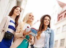有旅游书的三个美丽的女孩在城市 免版税库存图片