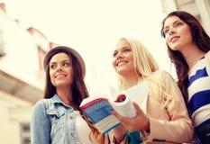有旅游书的三个美丽的女孩在城市 库存照片