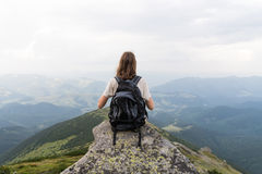 有旅游背包的少妇采取小山的休息上面在喀尔巴阡山脉的并且享受美好的风景 图库摄影