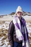有旅行在冬天山的帽子和毯子的年轻人 库存照片