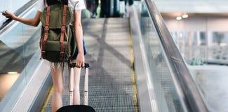 有旅行在机场的行李的中央部位妇女 库存照片