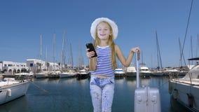 有旅行手提箱和手机的少年女孩在游艇风景的海港 股票录像