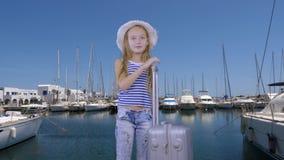 有旅行手提箱等待的船的旅游女孩在游艇背景的海港 股票视频