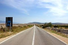有旅行标志和蓝山山脉的空的海岛路 免版税库存图片