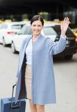 有旅行的微笑的少妇请求挥动的手 库存图片